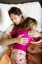 Overhead view of father sleeping with daughter on bed at home - CAVF05441