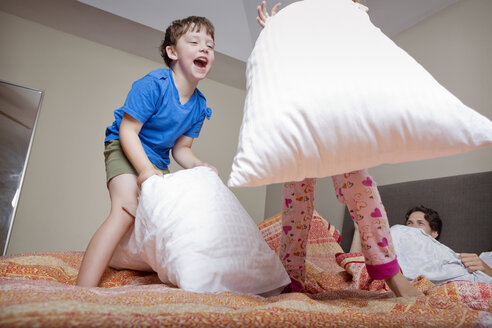 Low angle view of kids playing pillow fight - CAVF05444