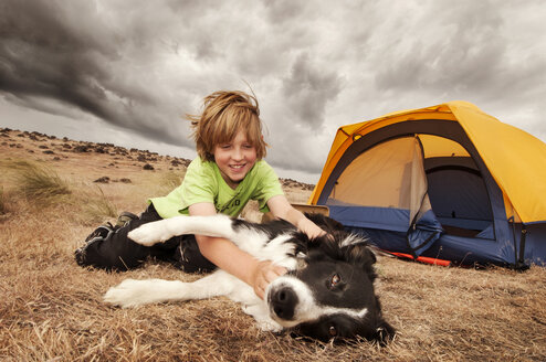 Boy playing with dog while sitting by tent on field - CAVF05501