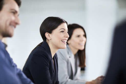 Smiling businesswoman listening in meeting - CAIF10651