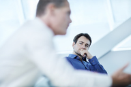 Attentive businessman listening to colleague in meeting - CAIF10657
