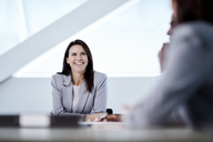 Smiling businesswoman listening in meeting - CAIF10681