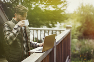 Man drinking coffee and using laptop on cabin deck - CAIF10702