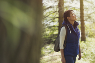 Woman hiking with backpack looking up in woods - CAIF10705