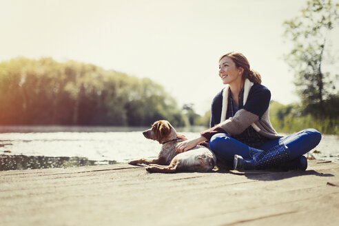 Smiling woman and dog relaxing on sunny lakeside dock - CAIF10708