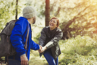 Smiling couple holding hands hiking in woods - CAIF10711