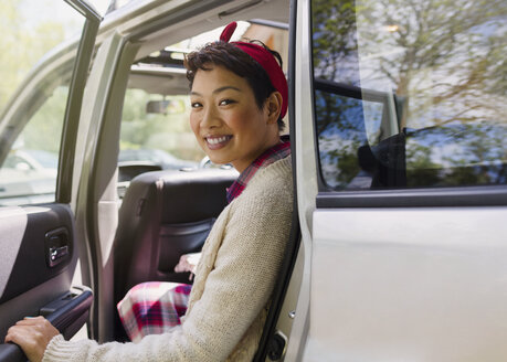 Portrait smiling woman getting out of car - CAIF10735