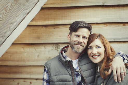Portrait smiling couple hugging outside cabin - CAIF10744