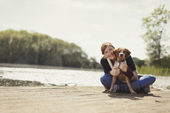 Portrait smiling woman hugging dog on sunny lakeside dock - CAIF10747