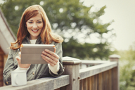 Smiling woman with red hair using digital tablet and drinking coffee at balcony railing - CAIF10753