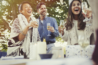 Friends laughing and drinking champagne at birthday party - CAIF10759