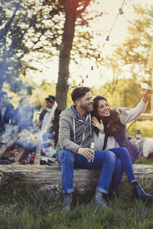 Couple posing for selfie with camera phone near campfire - CAIF10762