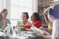 Women friends discussing book club book at restaurant table - CAIF10771