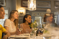 Smiling women friends looking away dining and drinking white wine at restaurant table - CAIF10774