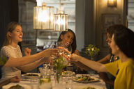 Smiling women friends toasting white wine glasses dining at restaurant table - CAIF10780