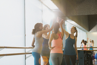Women high fiving in sunny gym studio - CAIF10792