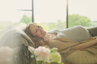 Portrait smiling pregnant woman laying on sofa - CAIF10807