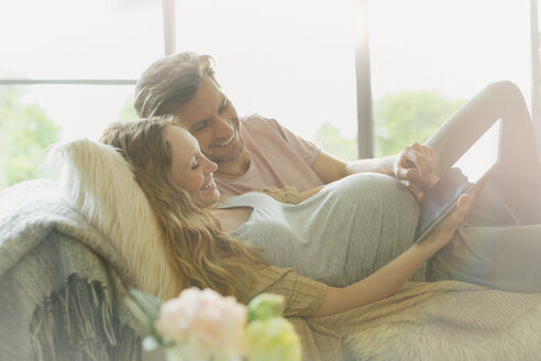 Pregnant couple laying relaxing using digital tablet - CAIF10816
