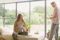 Pregnant couple eating cereal and drinking coffee in living room - CAIF10822