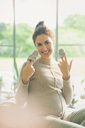 Portrait smiling pregnant woman holding baby booties - CAIF10831