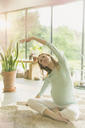Pregnant woman practicing yoga doing side stretch - CAIF10846