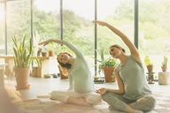 Pregnant women practicing yoga doing side stretch - CAIF10876
