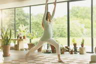 Pregnant woman practicing yoga warrior 1 pose - CAIF10879