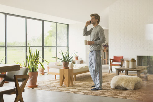 Man in pajamas talking on cell phone and drinking coffee in living room - CAIF10900