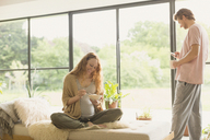 Pregnant couple eating and drinking coffee in living room - CAIF10906