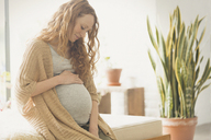 Pregnant woman holding stomach - CAIF10912