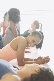 Smiling women talking on yoga mats in exercise class gym studio - CAIF10936