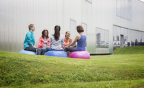 Women on fitness balls talking in exercise class on gym lawn - CAIF10939