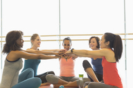 Smiling women touching hands in exercise class gym studio - CAIF10957