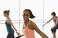 Portrait enthusiastic woman jumping rope in exercise class gym studio - CAIF10972