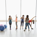 Women stretching and drinking water in exercise class gym studio - CAIF10981