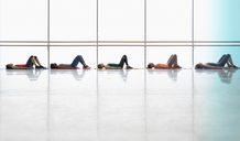 Women resting laying on yoga mats in exercise class gym studio - CAIF10987