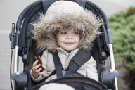Smiling girl in fur hood riding in stroller - CAIF11059