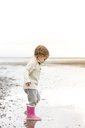 Girl in pink rain boots playing in water on beach - CAIF11065