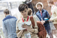 Young woman using digital tablet at technology conference - CAIF11098