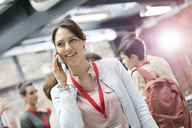 Smiling businesswoman talking on cell phone at conference - CAIF11104