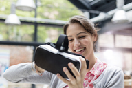 Smiling woman trying virtual reality simulator glasses at technology conference - CAIF11110