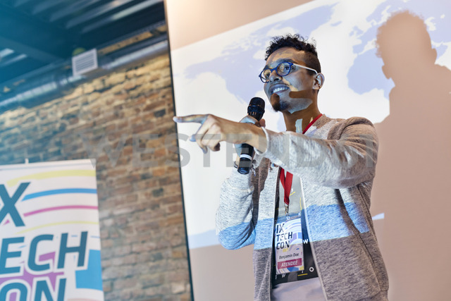 Speaker with microphone in front of projection screen at technology conference - CAIF11134