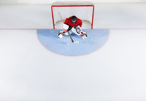 Hockey goalie in red uniform protecting goal net - CAIF11146
