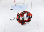 Overhead view hockey team in red uniforms huddling on ice - CAIF11149