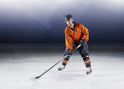 Portrait confident hockey player in orange uniform on ice - CAIF11155
