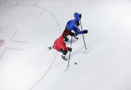 Hockey players going for the puck on ice - CAIF11164