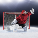Hockey goalie in red uniform reaching for puck with glove at goal net - CAIF11176