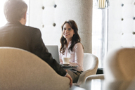 Smiling businesswoman listening to businessman in lobby - CAIF11182