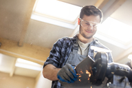 Smiling metal worker using sander in workshop - CAIF11206