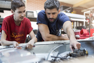 Father and son fixing car engine - CAIF11224